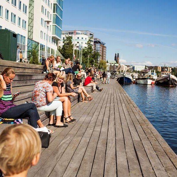 Människor solar på brygga vid vattnet
